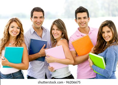 Happy group of students holding notebooks outdoors