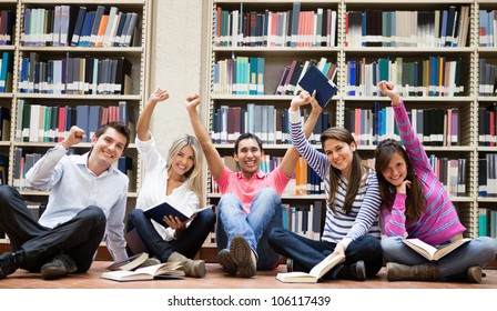 Happy group of students at the library with arms up