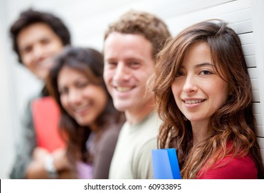 Happy group of students with notebooks against a wall