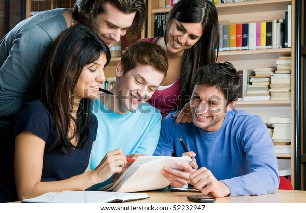 Happy group of students studying and working together in a college library
