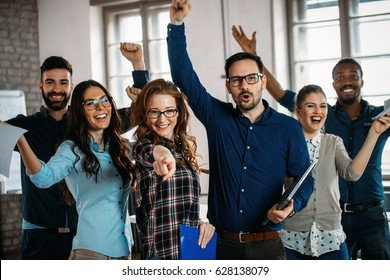 Happy group of successful company employees in office