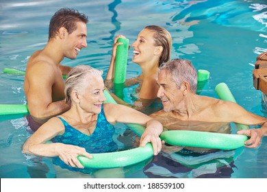 Happy group in swimming pool doing aqua fitness with swim noodles