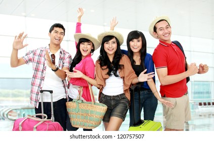 Happy group of tourists looking to camera and smile