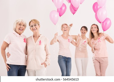 Happy group of women with pink balloons in anticancer campaign