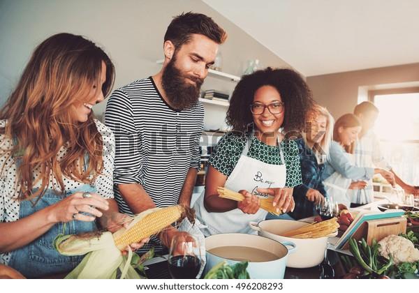 Glückliche Gruppe junger erwachsener Männer und Frauen, die zu Hause in der kleinen Küche oder im kulinarischen Unterricht zusammen kochen