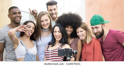 happy group of young friends taking a selfie photo with funny faces using a cell phone opn selfie stick. concept of diversity friendship and carefree lifestyle of university students.