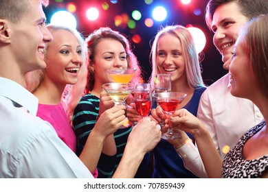 Happy group of young friends touching the glasses with each other