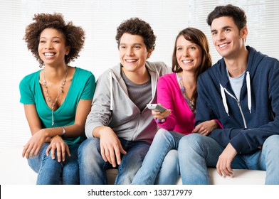Happy Group Of Young Friends Watching Television At Home
