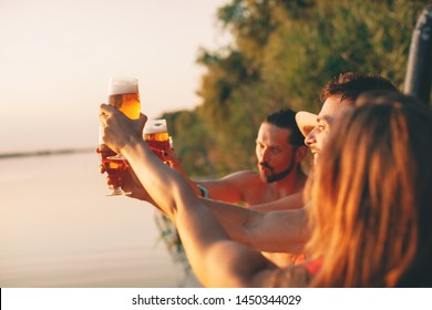 Happy group of young people drinking beer on a dock by the river during the summer sunny day