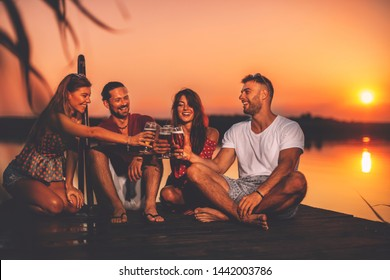 Happy group of young people toasting with beer on a dock by the river during the summer sunset. Selective focu on glasses