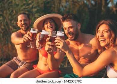 Happy group of young people toasting with beer on a dock by the river during the summer sunny day