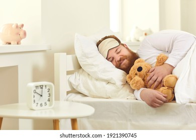 Happy grown-up man sleeping in good comfortable bed with cute teddy bear. Funny guy lying on white pillows and dreaming sweet dreams in deep sleep at 10 am in Covid-19 lockdown or on weekend morning