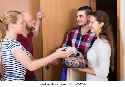 Happy guests with presents and cake standing in doorway. Focus on girl