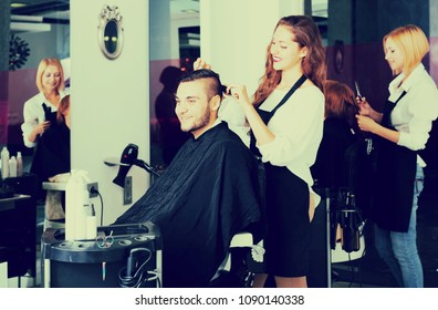 Happy guy cuts hair at the hair salon