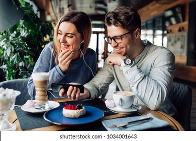Happy guy and girl in headphones, watching a movie on mobile phone, cheerfully laughing while sitting at cafe and drinking coffee.