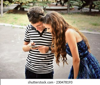 Happy guy and girl  looking at mobile phone