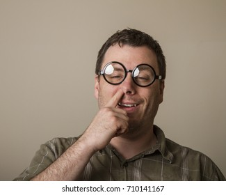 Happy guy with glasses putting his finger up his nose