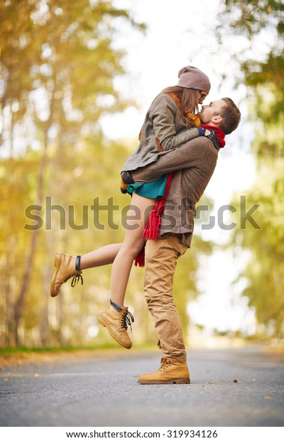 Happy guy holding his girlfriend during date in park