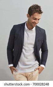 Happy guy in jacket, hands in pockets, smiling