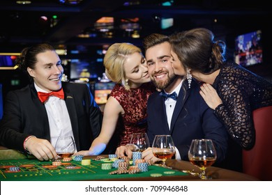 Happy guy was kissed by two beautiful girls after win in roulette