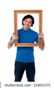Happy guy looking through empty picture frame