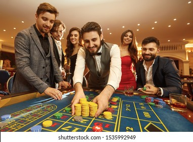 Happy guy playing gambling at a casino roulette
