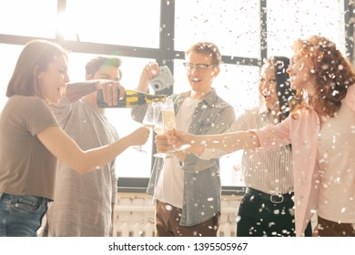Happy guy pouring champagne for his friends while other young man shooting this on photocamera at home party
