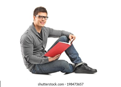 Happy guy reading a book seated on the floor isolated on white background