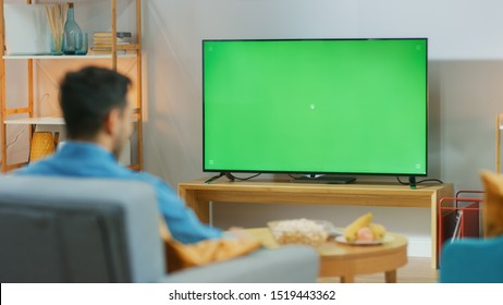 Happy Guy Sitting At Home in the Living Room on His Chair, Watching Green Chroma Key Screen, Relaxing After Work. Man in a Cozy Room Watching Sports Match, News, TV Show or Movie.