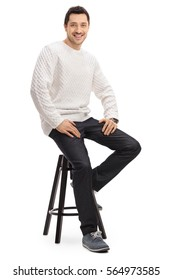 Happy guy sitting on a chair and looking at the camera isolated on white background