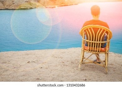 Happy guy sitting on a stool by the sea background on the nature