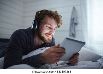 Happy guy with touchpad watching movie in bed