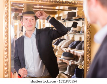 happy guy try on trilby hat and looking at mirror in headwear store