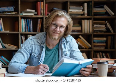 Happy guy university student study in library learning holding book doing work assignment looking at camera sit at desk, smiling young man teacher wear glasses preparing writing course, portrait