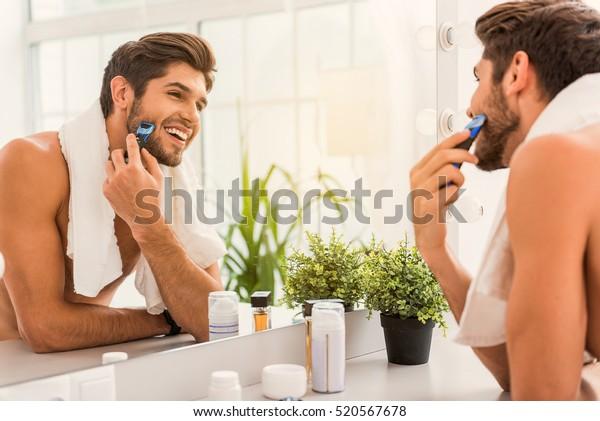 Happy guy using electric razor