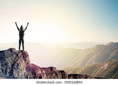 Happy hacker on cliff with clouds and copy space. Success and victory concept