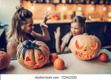 Happy Halloween! Attractive young woman with her little cute daughter are preparing to Halloween on kitchen. Mom with daughter are having fun with pumpkins.