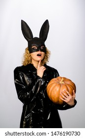 Happy Halloween. Beautiful woman in halloween bunny costume holds pumpkin. Sexy blonde girl in rabbit black mask with pumpkin. Sexy female model in Easter bunny black rabbit mask with jack-o-lantern.