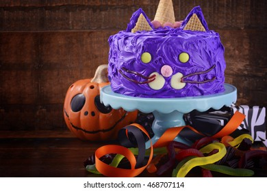 Happy Halloween cat cake party food with purple frosting and candy decorations on dark wood background.