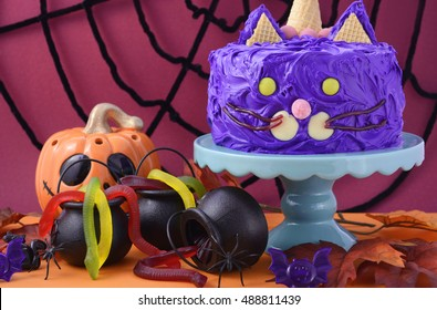 Happy Halloween cat cake party food with purple frosting and candy decorations with colorful party table ad spider web background.