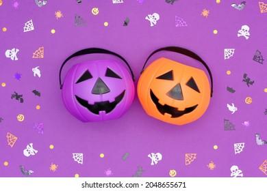 Happy Halloween concept. Jack O' Lantern Halloween pumpkin pails on purple background. Orange and purple plastic Trick Or Treat candy bucket inside a frame made of pinata confetti.