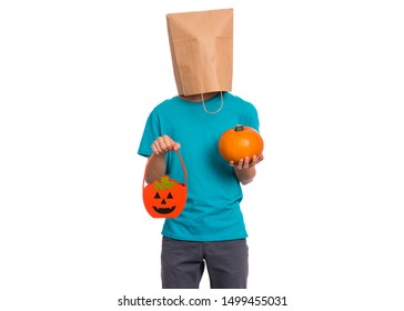 Happy halloween concept. Teen boy with paper bag over his head holds orange pumpkin bucket and small pumpkin, isolated on white background. Teenager cover head with bag. Child waiting candy.