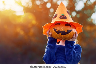 Happy Halloween! Cute little child with a pumpkin in the park.