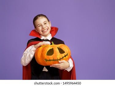 Happy Halloween! Cute little Dracula with a pumpkin on purple background.
