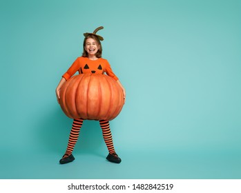 Happy Halloween! Cute little girl in pumpkin costume on turquoise background.