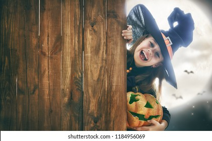 Happy Halloween! Cute little witch with pumpkin. Beautiful young child girl in costume on full moon background. Space for text.