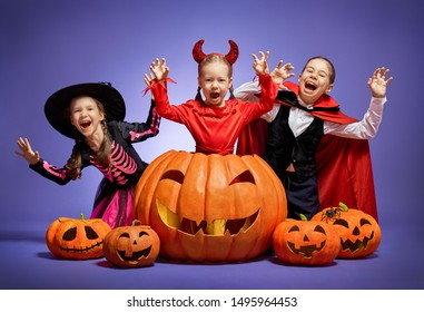 Happy Halloween! Cute little witch, Dracula and devil with pumpkins on purple background.