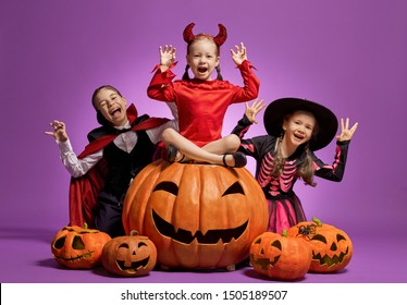 Happy Halloween! Cute little witch, Dracula and pumpkin on purple background.
