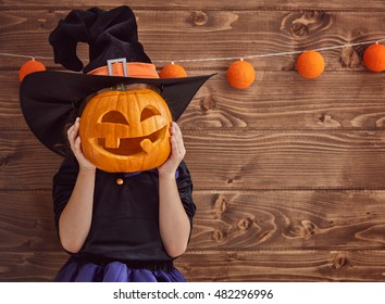 Happy Halloween! Cute little witch with a pumpkin.