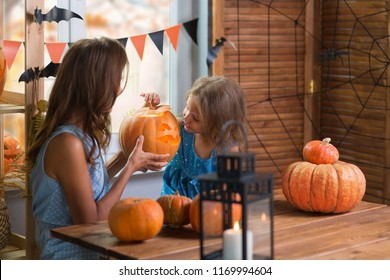 Happy Halloween. Family little beautiful girl with mother celebrating home in interior with pumpkins